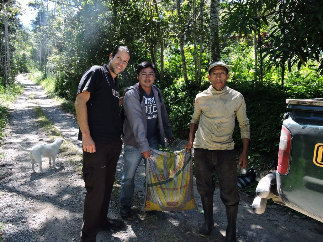 Ronald delivers 10 kg of a biochar formulation to Dennis, a participant farmer -- Ruy and the dog behind are just there for the picture
